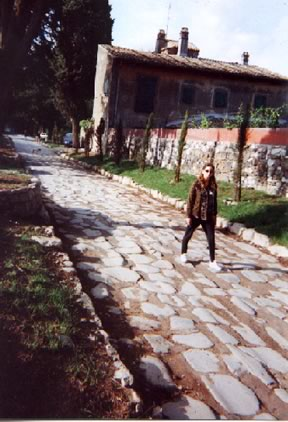 Bettina Drummond strolling along a portion of the Via Appia, an example of the Roman network of roads that spanned from one end of the empire to the other.