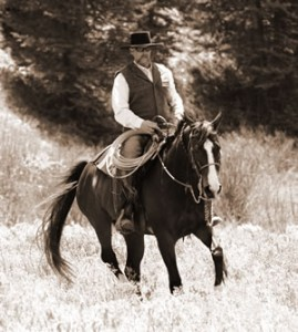 Jim on an American Warmblood Esprit moving through the sagebrush. Esprit is an FEI Level competition dressage horse.